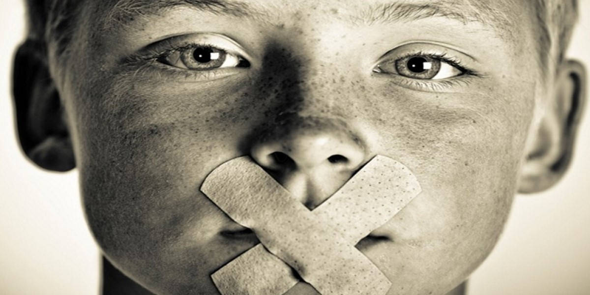 A young person with bandages criss-crossed over his mouth, signifying his lacking a voice in his therapeutic services